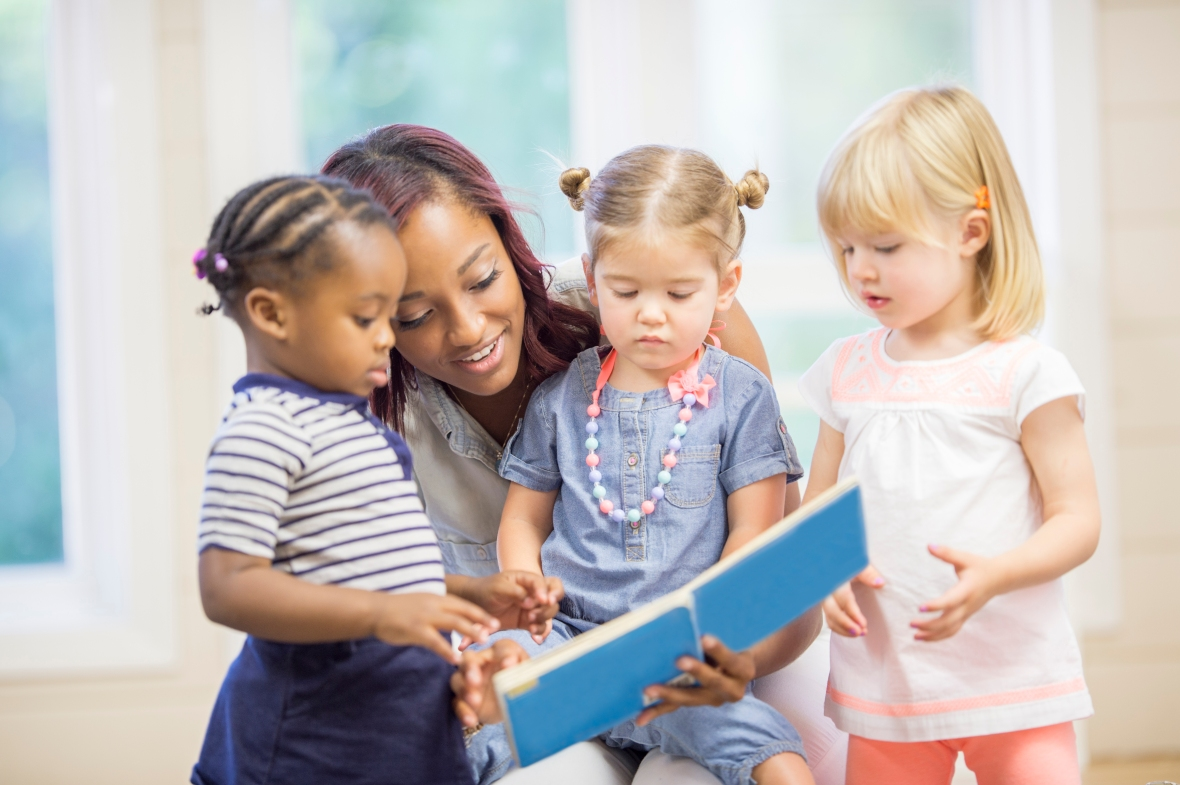 A multi-ethnic group of toddlers are sitting with their teacher and are listening to her read a book.
