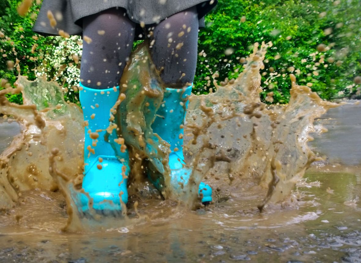 28837630 - child wearing blue rain boots jumping into a puddle. close up